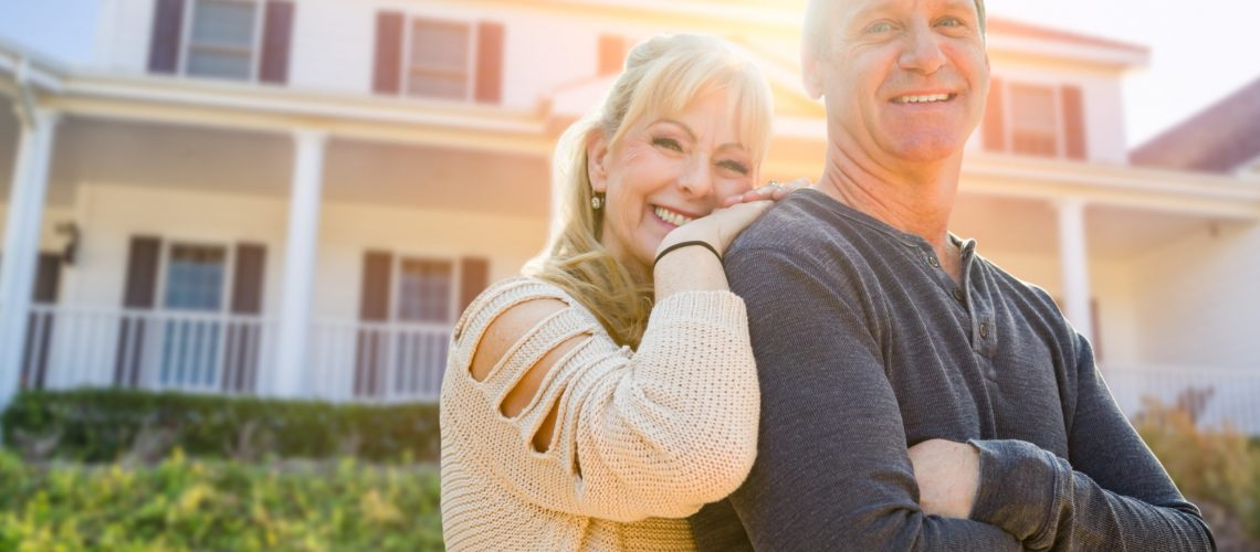 Attractive Middle-aged Couple In Front Of Their House.