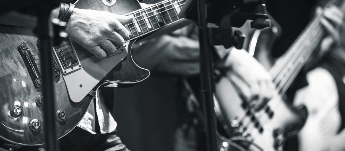 Rock and roll music background, guitar players on a stage, monochrome photo with selective focus